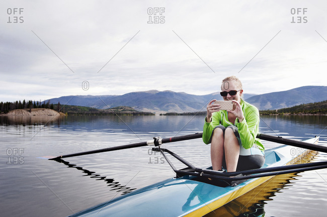 A woman takes a picture with her phone while in a kayak