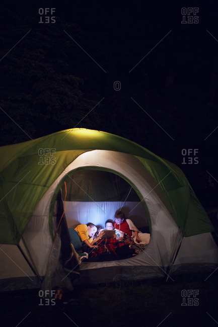 Kids looking at a smart tablet in their tent