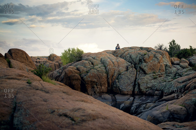 A man sits on a large rock in the desert