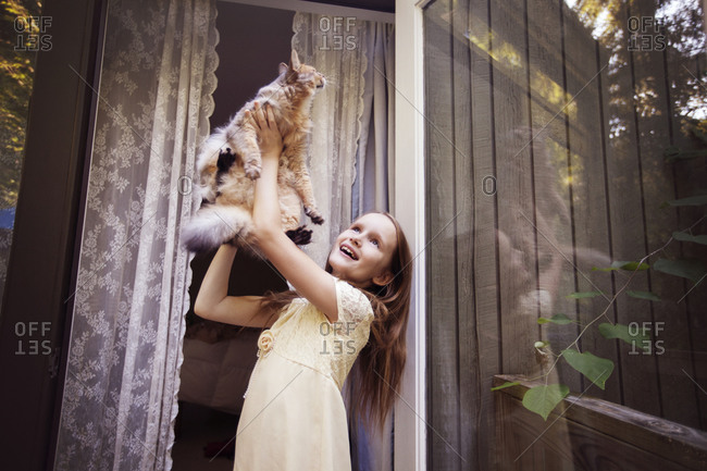 Young girl lifting her cat in the air