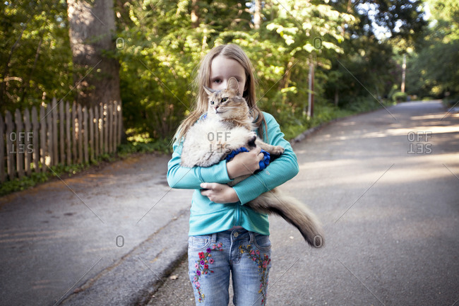 Girl carrying her cat down a street