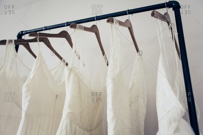 Five styles of white wedding dresses hanging on rack