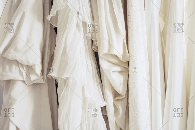 Hanging row of white wedding gowns