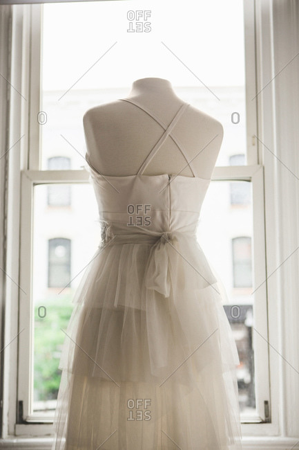 Back view of wedding gown on a dress form in front of window