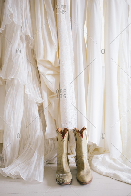 Pair of worn white cowboy boots in front of wedding gowns