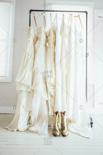 Cowboy boots on floor in front of rack of wedding gowns