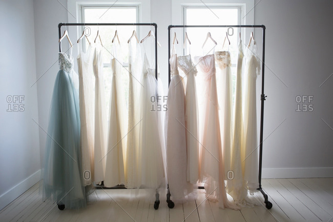 Two racks of wedding gowns on racks in front of window