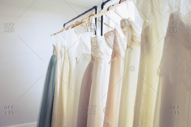 White and pastel colored wedding dresses on rack