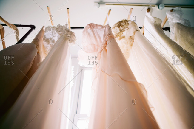 Low angle view of wedding gowns handing on rack in front of window