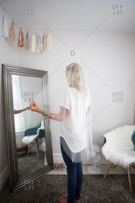 Woman trying on wedding veil in front of mirror