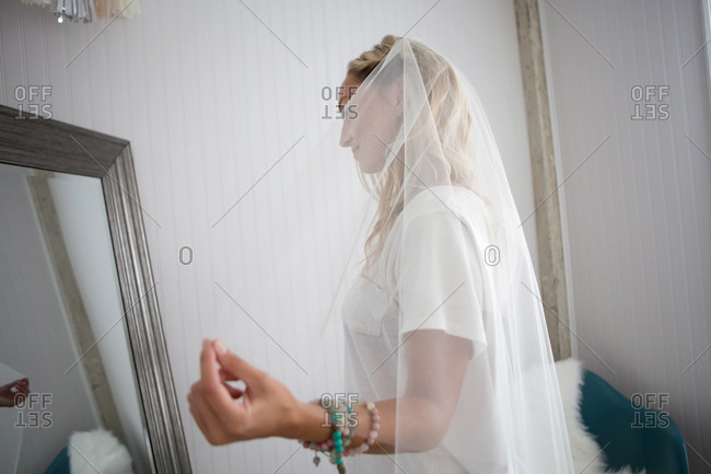 Woman gazes at herself in mirror as she tries on wedding veil