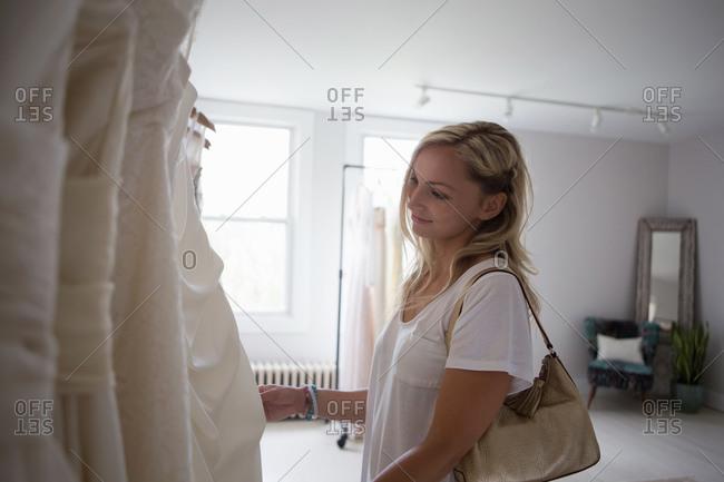 Woman admiring wedding dress in bridal studio