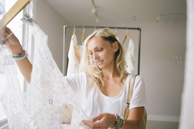Woman examines lace garment in bridal boutique