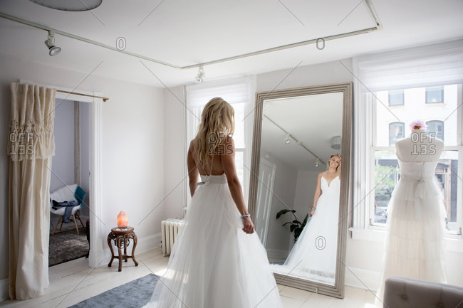 Woman trying on wedding dress admires her reflection in mirror