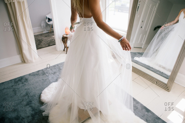 Woman trying on wedding dress in front of mirror