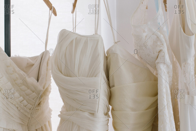Detail of wedding dresses hanging on rack