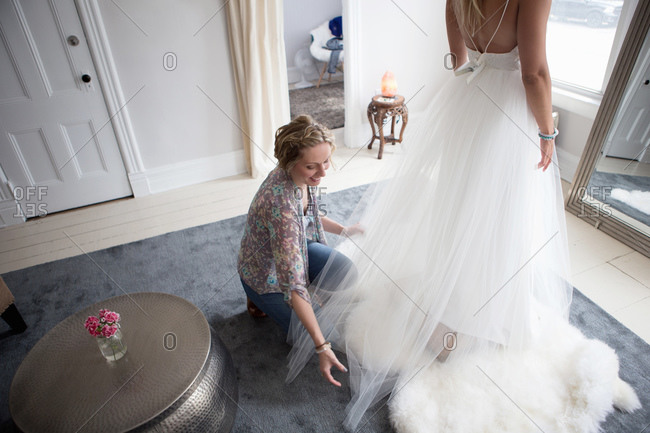 Fashion designer adjusts the tulle skirt of dress with a client