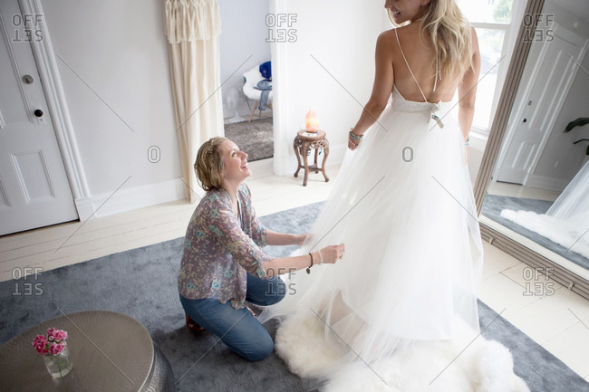 Shop owner helps woman try on wedding gown