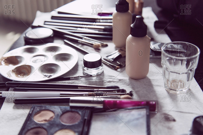 Elevated view of makeup artist's work table with cosmetics and brushes