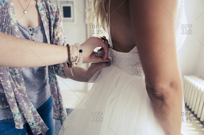 Shop owner clips the back of wedding dress customer is trying on