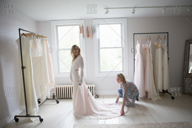 Designer spreads out the train of customer's wedding gown