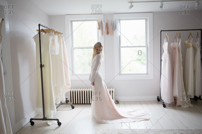 Woman admires the train of white lace gown in bridal boutique