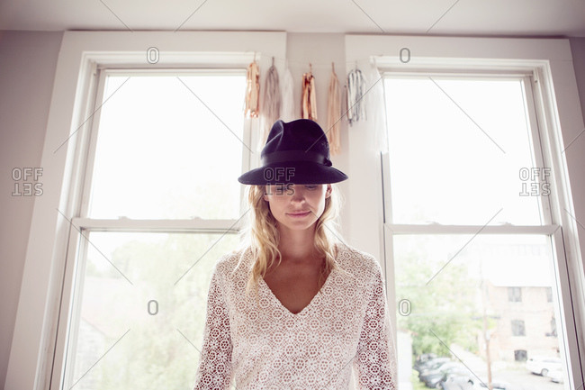Woman in white lace and black fedora standing in front of windows