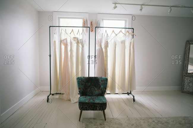 Chair in front of two racks of wedding dresses bridal boutique