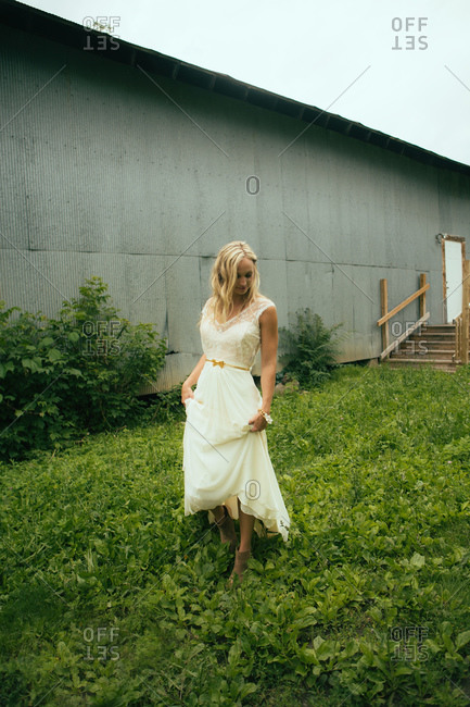 Woman in beautiful wedding dress walking in grass outside rustic metal shed