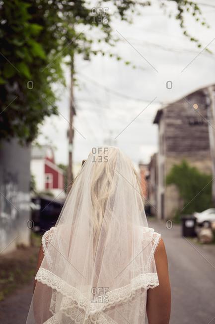 Back view of bride in veil and gown walking down alleyway behind buildings