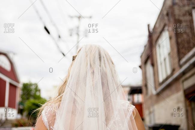 Back view of woman in wedding dress standing on street of small town