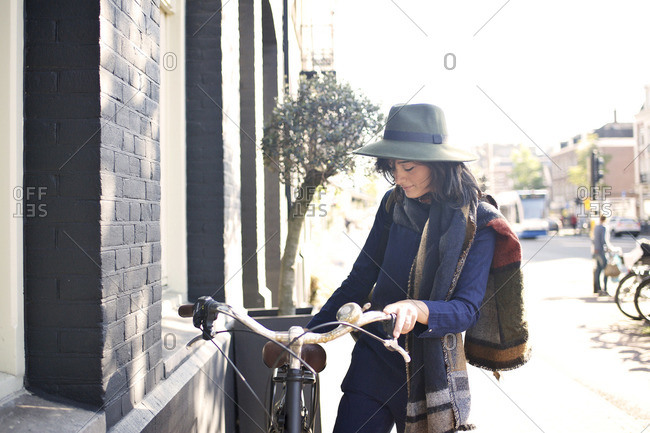 Woman leaning her bike against a brick building