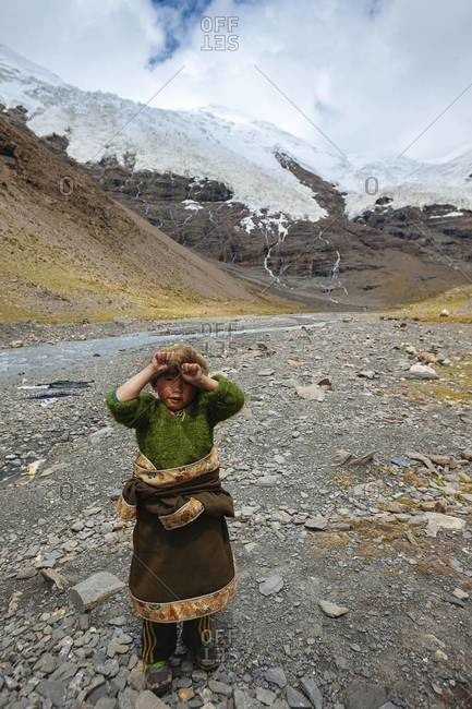 Mount Everest, Tibet - August 28, 2013: A Tibetan child standing in front of a glacier