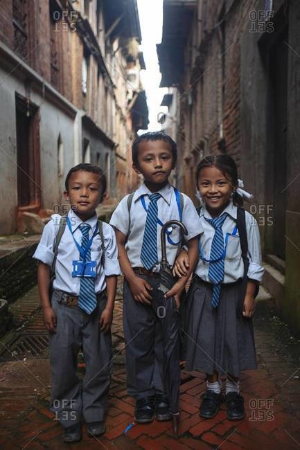Bhaktapur, Nepal - September 3, 2013: Three students on their way to school in the city of Bhaktapur