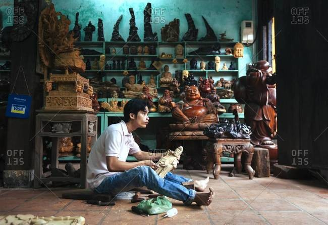 Hoi An, Vietnam - January 17, 2014: A man in a store carves a Hindu sculpture