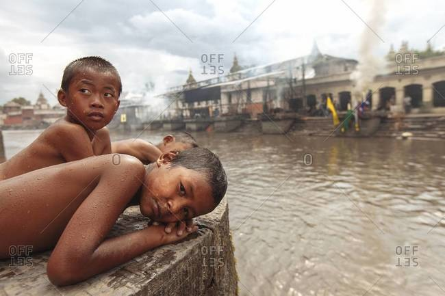 Kathmandu, Nepal - September 1, 2013: Boys lay down by a river in Tibet