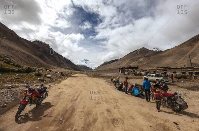 Motorbikes parked along the edge of a dirt road in Tibet