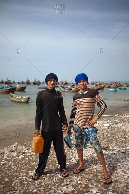 Mui Ne, Vietnam - January 14, 2014: Two young men stand on the shore in Vietnam