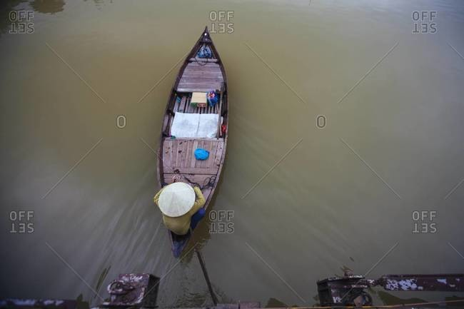 A man unties his boat from the harbor in Vietnam