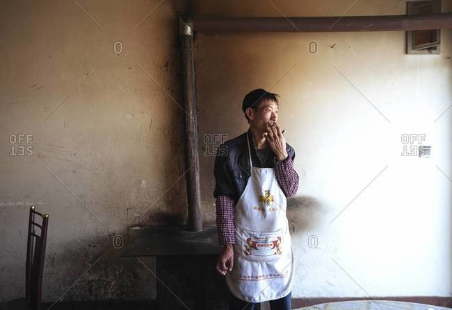 Xinjiang Province, Tibet - August 30, 2014: An old man in an apron smokes a cigarette