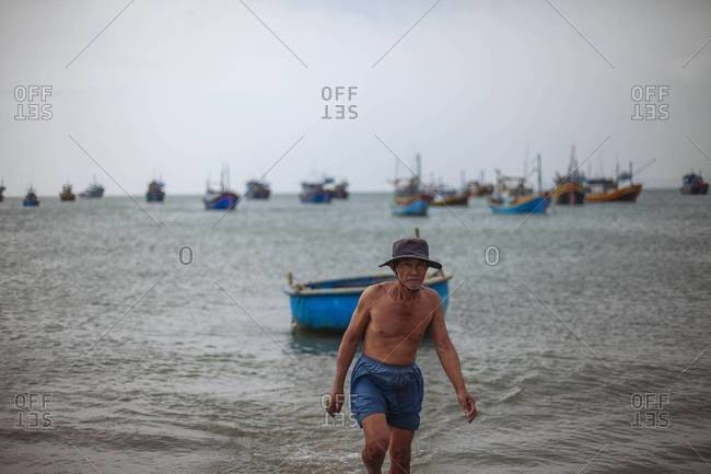 Mui Ne, Vietnam - January 14, 2014: An old man emerges from the water in Vietnam