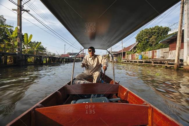 Damnoen Saduak, Thailand - December 4, 2013: A man drives a motorboat through a river in Cambodian