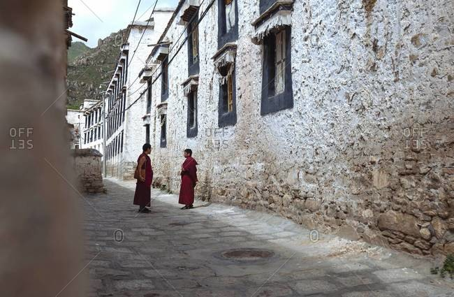 Lhasa, Tibet - August 26, 2013: Two monks meet on the street in Tibet