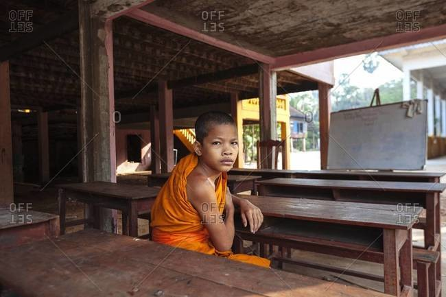 Siem Reap, Cambodia - December 25, 2013: A young Buddhist monk in an outside classroom