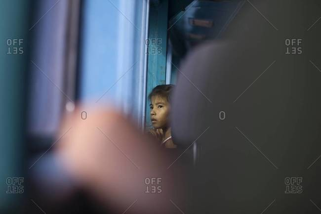 Krabi, Thailand - December 14, 2013: A young girl looks out of a window on a train