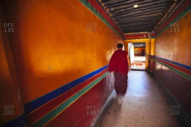 A Tibetan monk walks down a long corridor