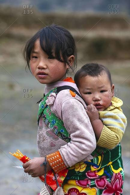 Sapa, Lao Cai Province, Vietnam - January 26, 2014: A young Vietnamese girl carrying her baby brother on her back in Sapa, Lao Cai Province in Northwest Vietnam