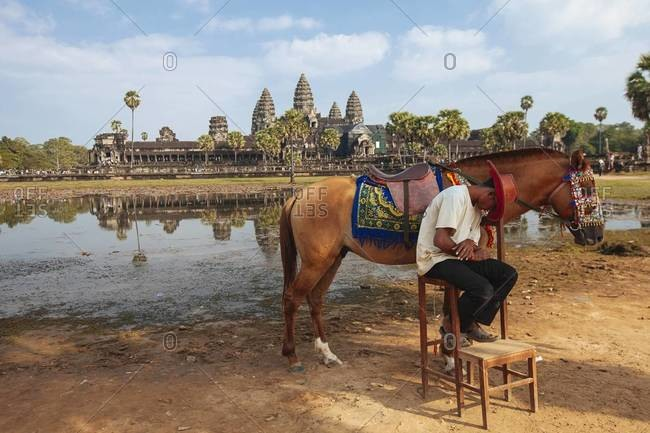 Siem Reap, Cambodia - December 28, 2013: A Cambodian man taking a nap next to his horse in the Angkor Wat Temple