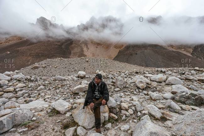 Mount Everest - Tibet - August 30, 2013: A Tibetan tour guide taking a break from hiking to the Mount Everest Base Camp