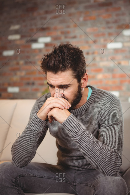 Stressed man with hands in front of mouth at home